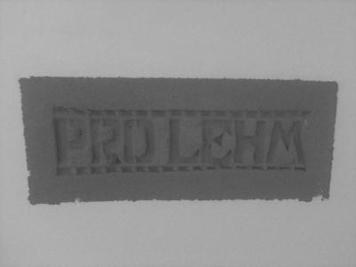 schriftzug-pro-lehm-in-lehmputzwand-mit-weisser-lehmfarbe-schwarz-weiss-style.jpg